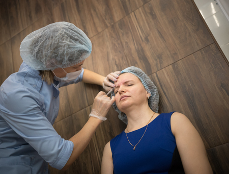 Woman in a cosmetology clinic. The specialist doing botox injections