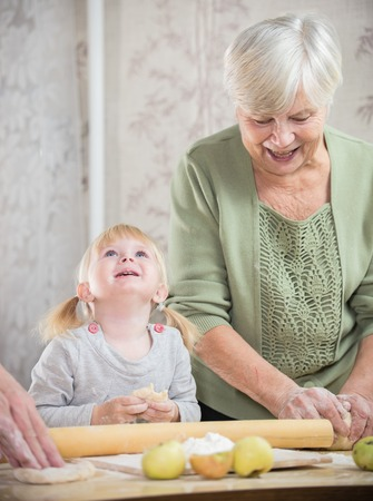 An old lady making little pies with a happy little girl. The girl looking up