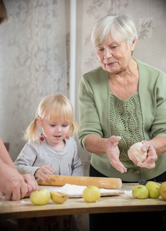 A grandmother and a granddaughter are making little pies
