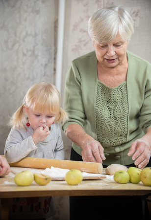 A grandmother and a granddaughter are making little apple pies Фото со стока