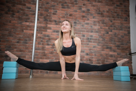 Joyful talented woman doing the splits in pole dance studio and smiling