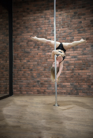 Blonde slim girl training pole dance in a studio