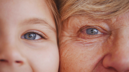Close up portrait of grandmother and granddaughter. Blue eyes