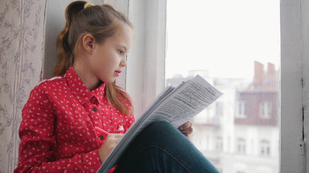 A little girl sitting on the window sill and drawing. Looking at the street Zdjęcie Seryjne