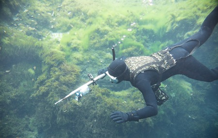 Spearfishing man with flashlight in deep of lake swimming with action camera and underwater gun 版權商用圖片