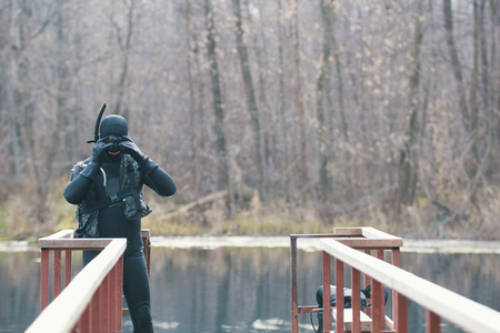 Fisherman in wetsuit and mask in preparation for a hunt. Autumn forest lake