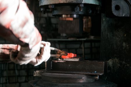 Blacksmith working with red hot metal workpiece of new axe on the anvil and electro hammer at the forge. Focus on anvil