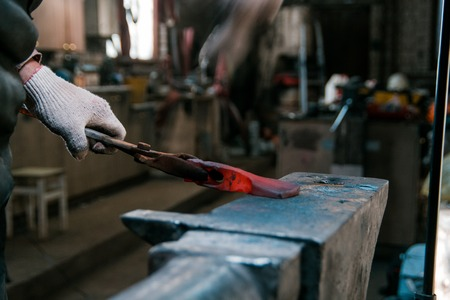 Blacksmith working with red hot metal workpiece of new axe on the anvil at the forge. Focus on hands
