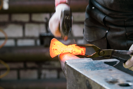 Blacksmith working with red hot metal workpiece of new axe on the anvil at the forge. Focus on red hot metal