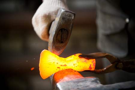 Blacksmith working with red hot metal workpiece of new axe on the anvil in the forge