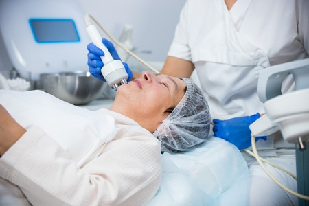 Cosmetology. Anti-aging procedure. Working with special instrument. Face smoothing
