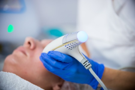 Cosmetology clinic. A client taking pore cleansing procedure. A woman cosmetologist working with a tool