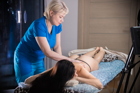 Massage session. A woman giving an anticellulite massage treatment. Wide shot Stock Photo