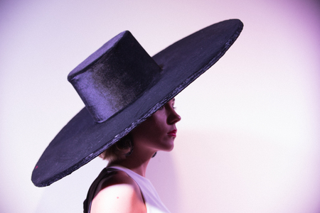 Young attractive woman standing on the background of a white wall in big hat Foto de archivo