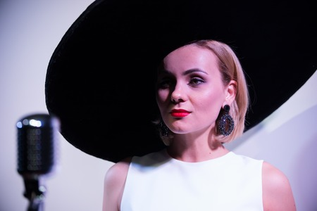 Young attractive woman standing near the mic on the background of a white wall in big hat.