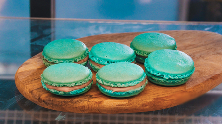 Blue pretty macaroons on a wooden stand behind the shop window 免版税图像