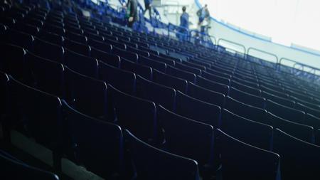 Preparing for a hockey match. Organizers walking around. Empty tribunes
