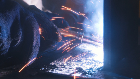 A welder in helmet doing his job. Welding process. Smoke and sparks. Close up