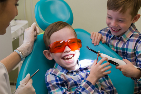 Reception at the dentistry. A smiling little boy lays on the couch and his brother staying next to him