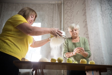 Two old women are making little apple pies. Sifting the flour Stockfoto
