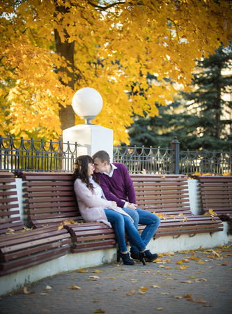 A couple in love sit on a bench and build each others eyes in the autumn park