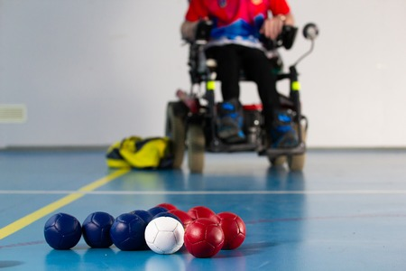 Boccia. A disabled sportsman sitting in a wheelchair. Close up of little balls for playing boccia. Tricolor.