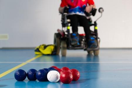 Boccia. Een gehandicapte sportman zit in een rolstoel. Close up van balletjes voor het spelen van boccia. Driekleur.