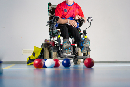 Boccia. A disabled sportsman sitting in a wheelchair in front of balls. Little balls for playing boccia.