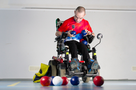 Boccia. A disabled sportsman sitting in a wheelchair holding little balls for playing boccia. Imagens