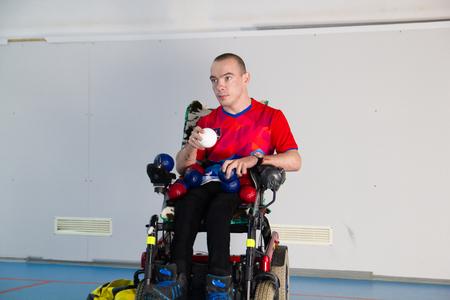 Boccia. A disabled man in a wheelchair. Holding a white little ball