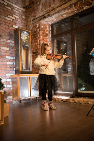 A little girl playing violin in an old flat
