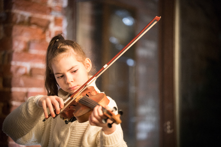 A little beautiful girl with long hair playing violin