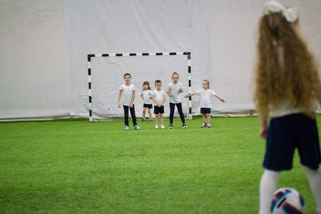 Children playing football indoors. Team protects the gates from a little girl attacking