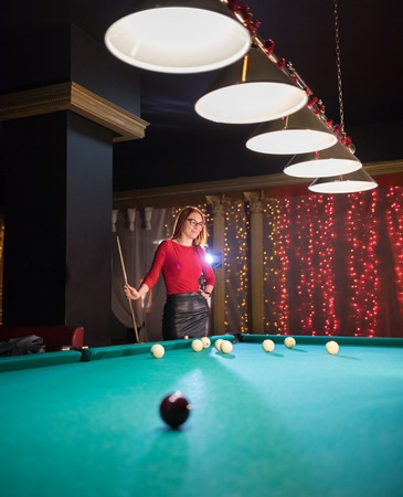 Billiard club. A woman with in glasses with red hair and nice figure standing by the table