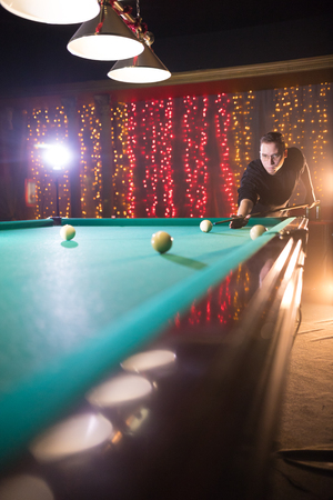 Entertainment concept. Concentrated young man in glasses playing billiard. Perspective