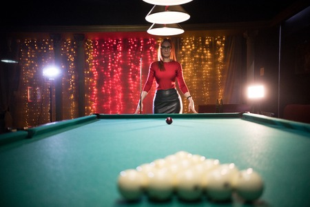 Billiard club. A woman with red hair and nice figure standing by the table