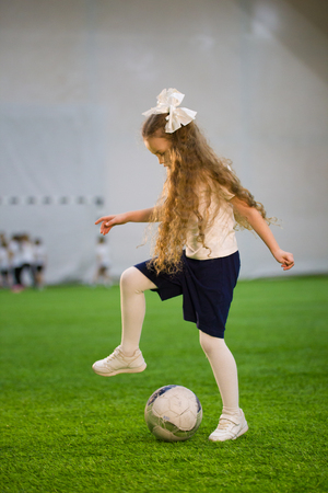 A little girl playing football holding your foot over the ball Stock Photo