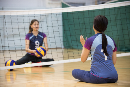 Sports for disabled people. Two young women sitting on the floor and playing volleyball. A woman with ponytail.