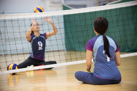 Sports for disabled people. Training. Two young women sitting on the floor and playing volleyball.