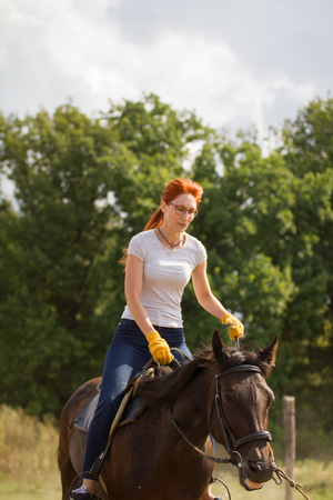 A redhead woman in white t-shirt riding a horse in nature.
