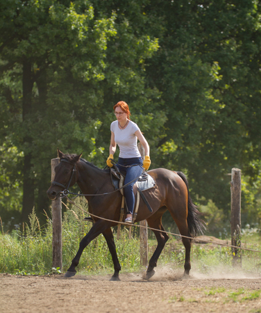 A redhead woman in white t-shirt and glasses riding a horse in nature. Фото со стока