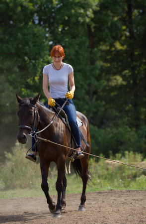 A redhead woman in white t-shirt and yellow gloves riding a horse in forest