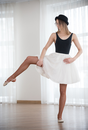 Ballerina in a hat bends a leg to the side, in the studio Stock Photo