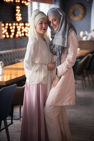 Two young muslim smiling women wearing scarf on the head standing in the cafe. Stock Photo