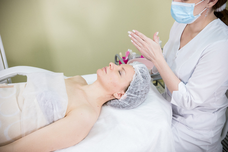 Cosmetologist prepares the clients face for cosmetic procedure of mesotherapy