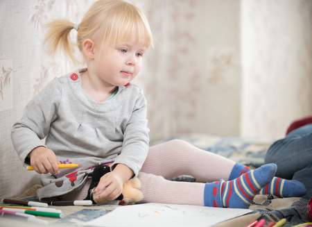 A little blonde baby girl in bright socks sitting on the bed