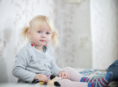 A little blonde baby girl sitting on the bed
