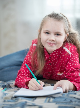 Girl spend time at home drawing while lying on the bed. Looking in the camera