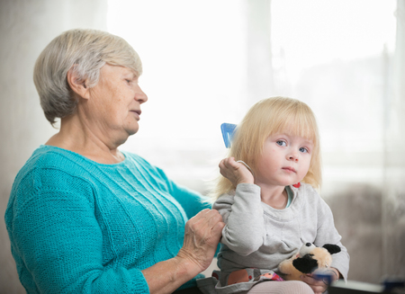 Grandmother combing blonde hair to her little granddaughter Stock Photo