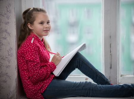 A little girl sitting on a window sill Stock Photo